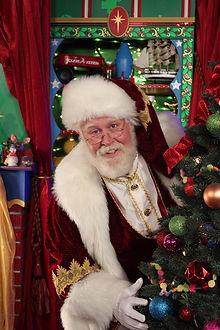Santa peering around a Christmas tree