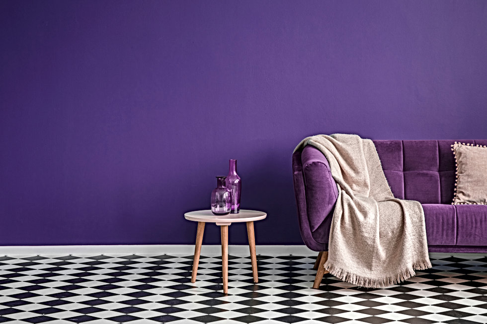 Dark purple sofa with a blanket beside a