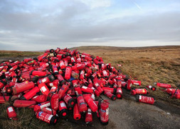 Hundreds of fire extinguishers have been dumped on a hill next to the M62