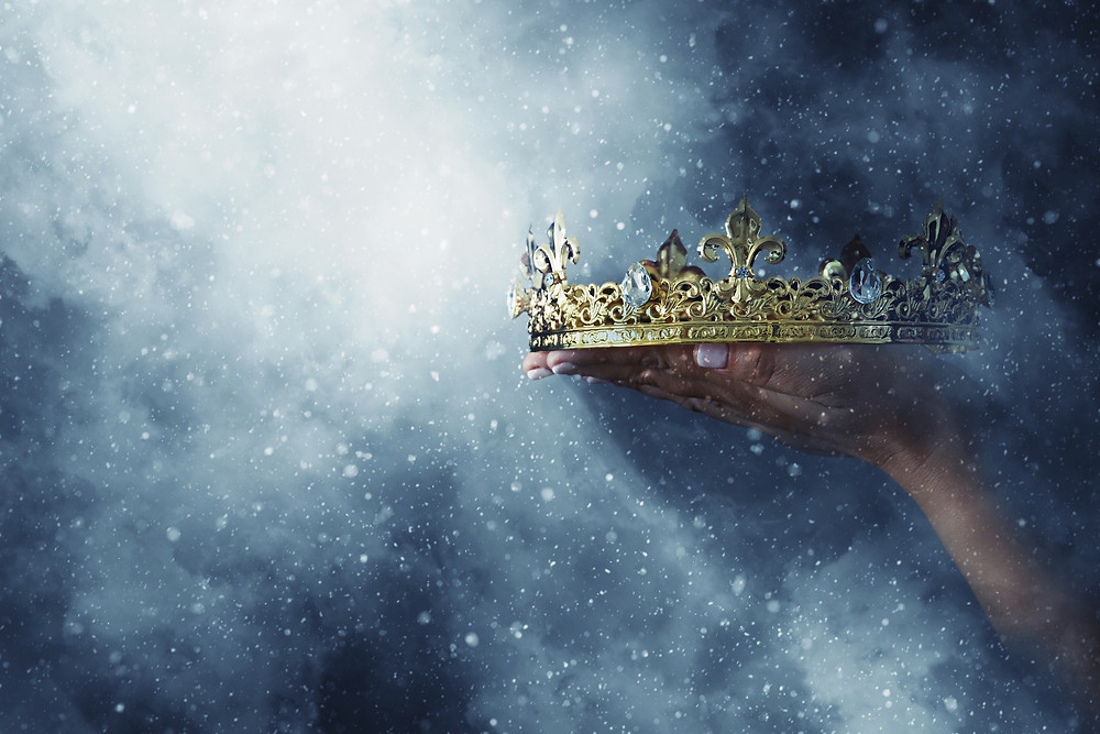 A gold and diamond crown gently held in a beautifully manicured female hand, with light and dust shining everywhere