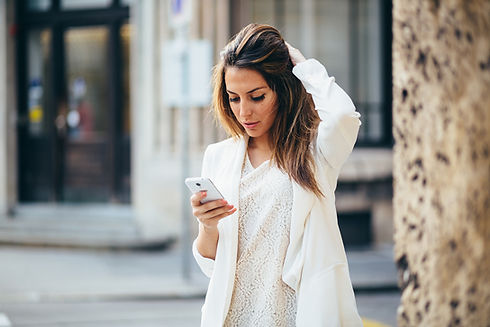 woman in white with mobile phone