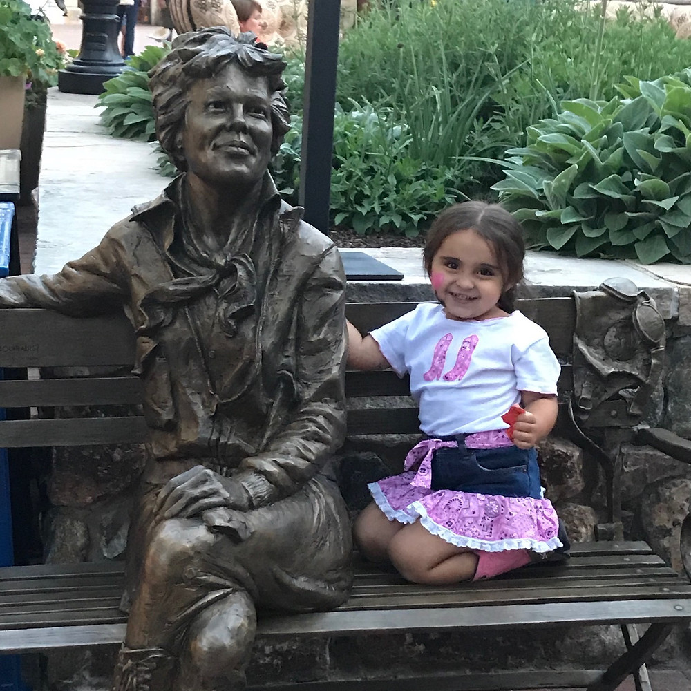 My daughter posing with a beautiful statue of Amelia Earhart in Colorado.