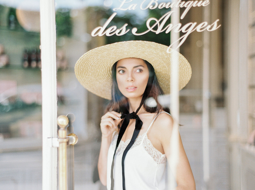 Girl behind the La Boutique des Angels ice-cream shop-window glass with hat