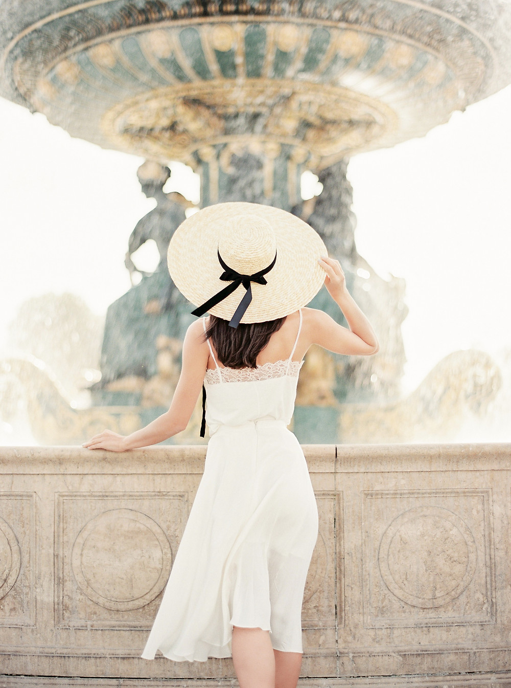 girl in white dress and hat at the fountain in Paris