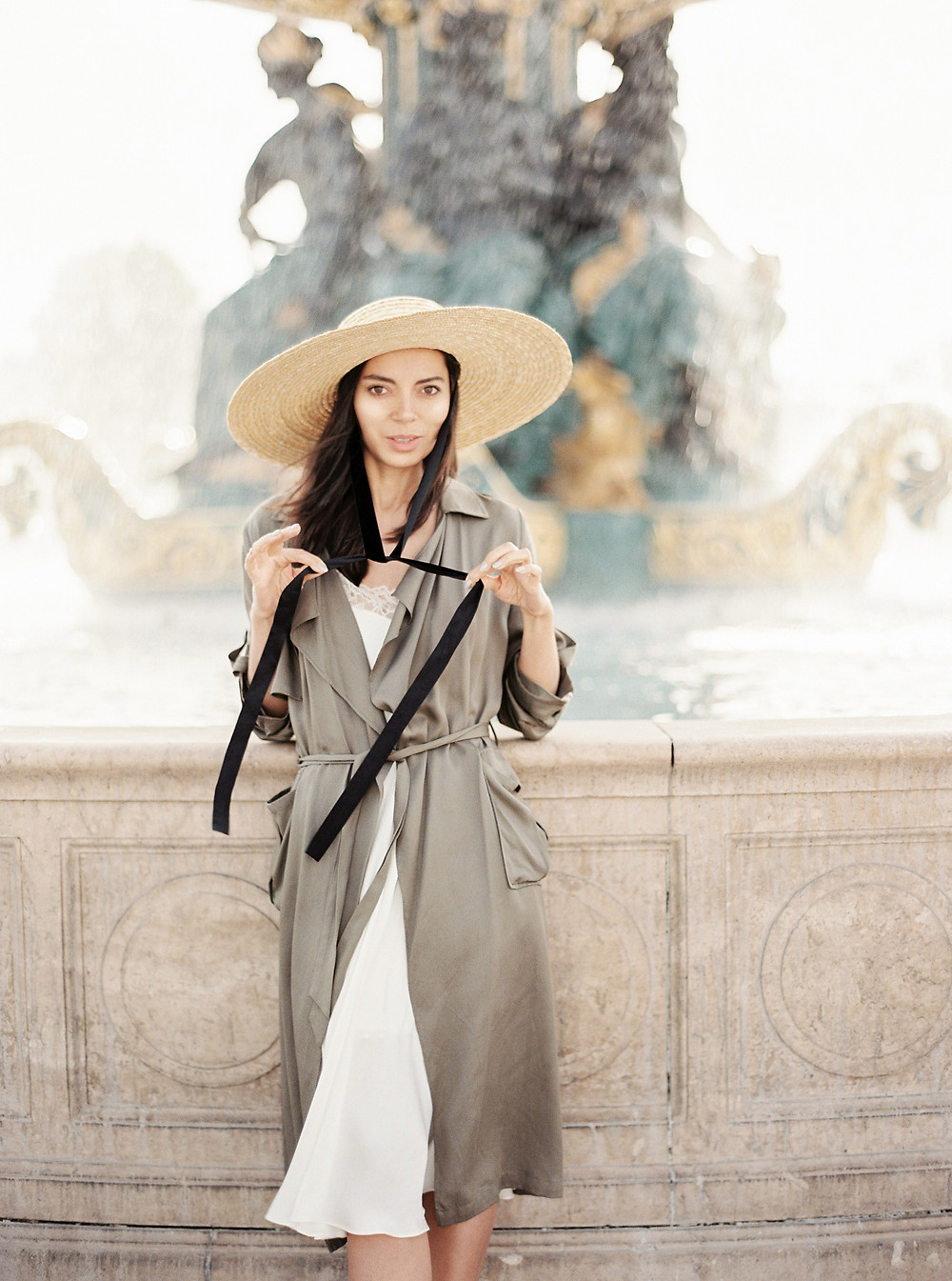 girl in white dress with trench-coat and hat at the fountain in Paris
