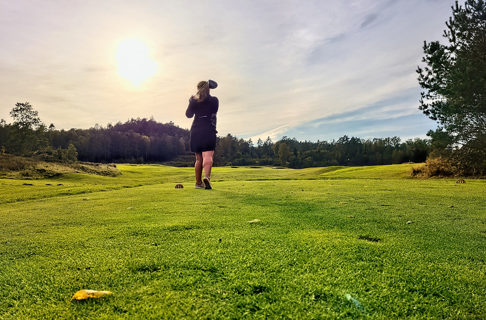 Woman golfing off the tee