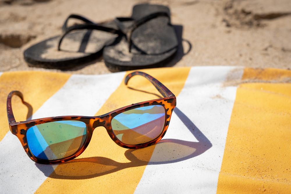 Sunglasses on a yellow striped beach towel.