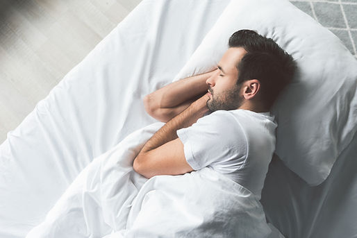Cute young man sleeping on bed.jpg