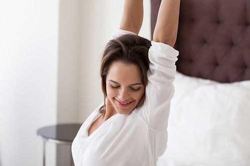 Smiling young woman stretching on cozy c