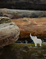 toy-figure-of-elephant-placed-on-log-on-