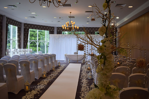 Ceremony Set up at the MacDonald Kilhey Court Wigan, with Chair Covers and Sashes, Aisle Carpet/Runner, Aisle Lanterns, Rose Petals, Aisle Podiums, Manzanita Trees, Led Backdrop Curtain, Light up Love Letters and Table Swagging.