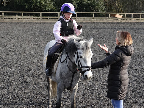 BSL PA signing to deaf girl on a horse