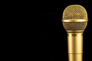 Golden microphone on black background..j