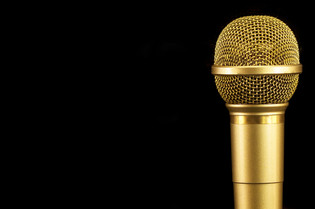 Golden microphone on black background..j