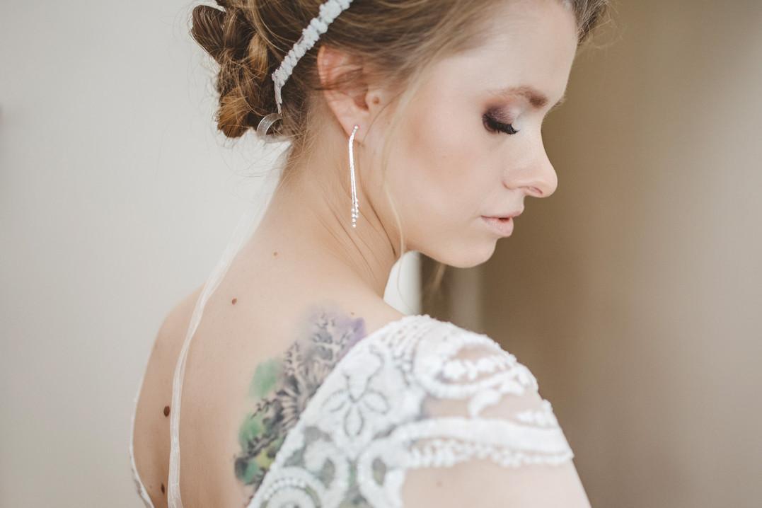 panna młoda zakłada kolczyk, biżuteria ślubna, kolczyki na ślub, opaska na głowę ślub, malowanie na ślub, makijaż na ślub, suknia ślubna, tatuaż na ślub, sesja w trakcie przygotowań, koronka ślubna