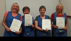 Four happy ladies receiving their certificates