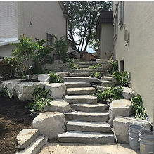 Armour stone step walkway between two homes leading to the backyard.  Plantings onn either side of steps