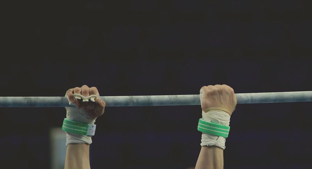 Deux mains accrochées à une barre d'athlétisme