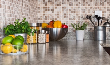 Kitchen worktop with bowls of fruit and veg
