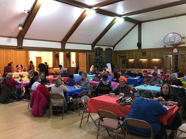 Holiday Dinner of Sharing tables filled with people in Church House