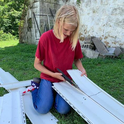 ASP member cutting siding