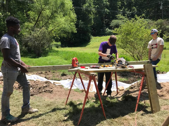 ASP team sawing wood to build stairs