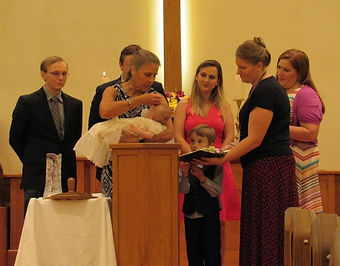 infant baptism with family surrounding the font