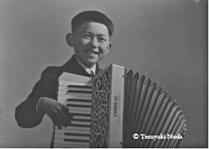 In 1948, 8years old; the second grade elemetary school playing the accoridon
