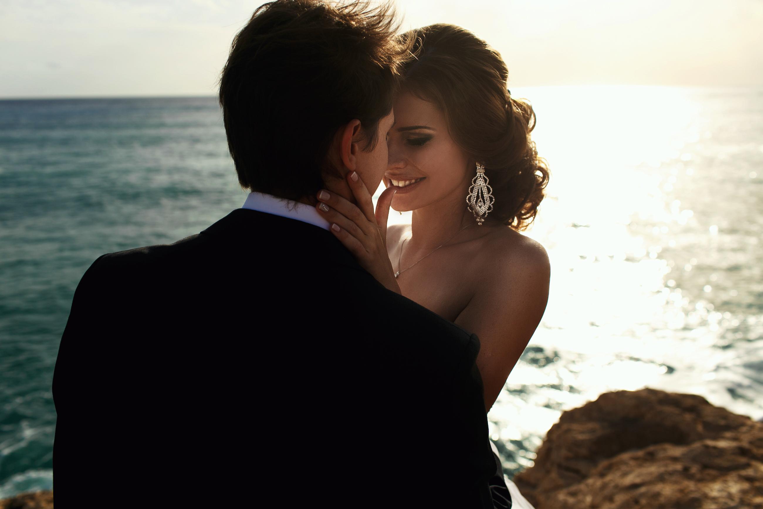 Happy stylish newlyweds on the beach nea