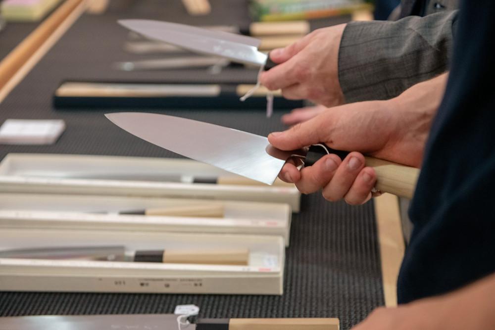 Personne choisissant un couteau japonais à l'Atelier DOMA