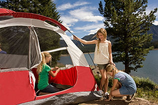 Young family setting up a tent by the lake