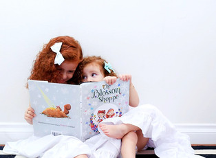 """Sisters, Jules and Kourtney, share a smile while reading """"The Blossom Shoppe""""."""