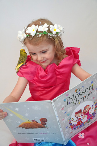 """Miriam reads """"The Blossom Shoppe"""" while wearing her Posie dress-up costume!"""