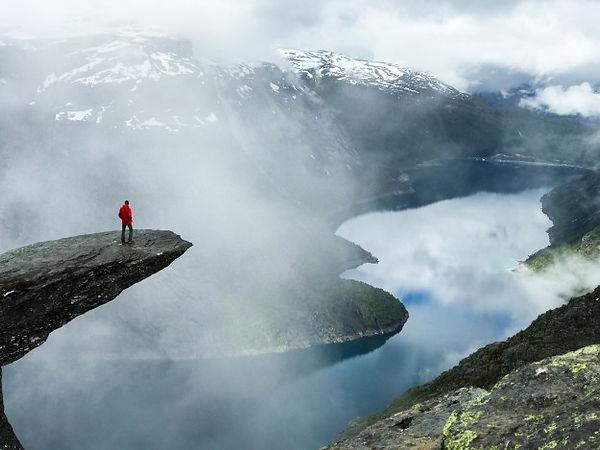 man-sits-end-trolltunga-before-mountains