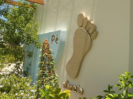Logomarca de Pé n'areia na parede da casa sede