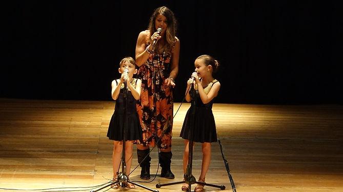 Un'insegnante di canto che canta con le sue piccole allieve, bambine di 6-7 anni