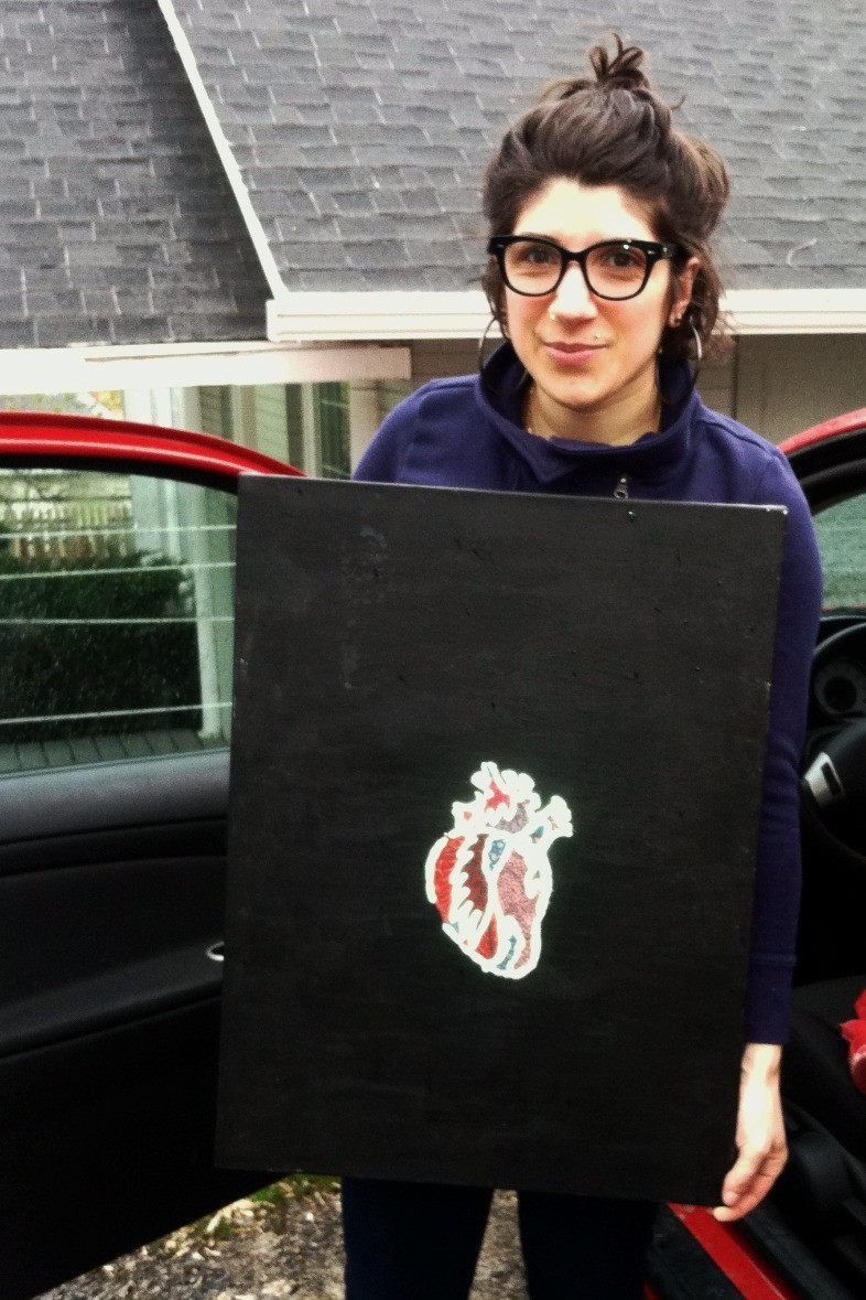 A woman wearing glasses and holding a canvas in front of her torso. the canvas is black with a red anatomical heart on it and the stitching outline around the details of the hear is glowing