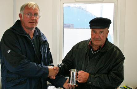 Commodore John Abernethy presents former Commodore John Lowrie Simpson with his service tankard.