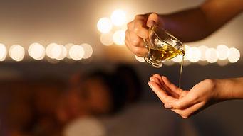 Masseur pouring massage oil, woman lying