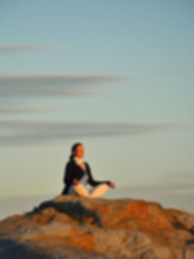Woman meditating on top of a mountain