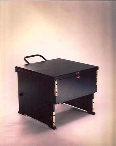 Modelo Malasaña. Cajón que se transforma en butaca con una posición intermedia como mesa auxiliar. Materiales: madera, hierro y tapicería de loneta. En esta foto, posición intermedia como mesa auxiliar