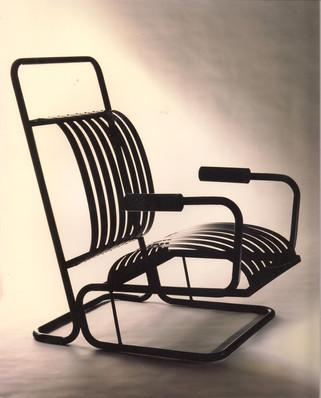 Modelo Ballesta. Butaca construida en fleje de acero negro y estructura de hierro pintado al horno en negro, rojo y gris perla