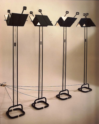 Lámpara con pantallas móviles que permiten proyectar la luz en cuatro direcciones. Estructura de hierro pintado al horno en negro, con el interior de las pantallas en blanco