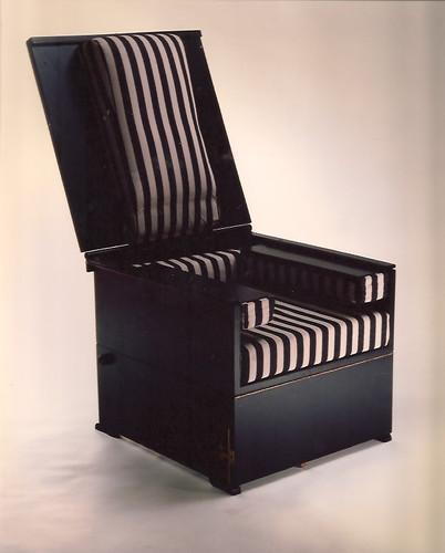 Modelo Malasaña. Cajón que se transforma en butaca con una posición intermedia como mesa auxiliar. Materiales: madera, hierro y tapicería de loneta. En esta foto, como butaca
