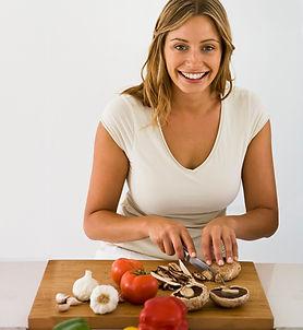 Woman cutting fresh whole food on a cutting board.