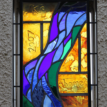 Stained glass panel in metal frame situated in external courtyard, East Lothian, 2017