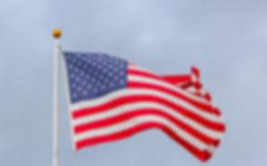 usa-flag-waving-on-white-metal-pole-1550