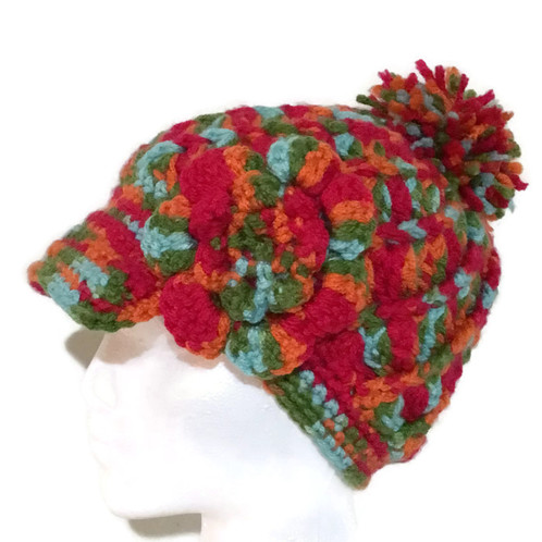 this beanie with cap newsboy hat was crochet from acrylic yarn the colors spun in this yarn are red orange light blue and green featuring a texture