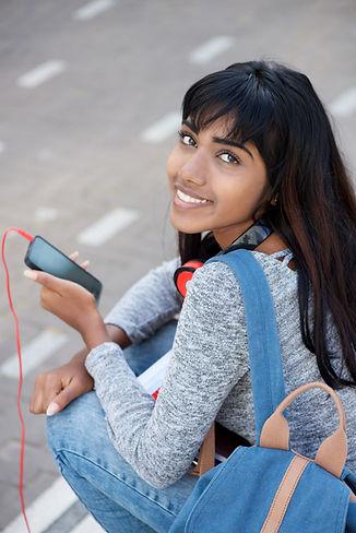 smiling-indian-female-student-holding-mo