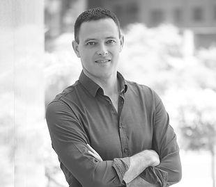 תמונה של אריאל אורבוך מתסכל למצלמה עם ידיים שלובות בצורת עיגול בשחור לבן